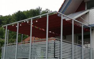 Rotes Raffsegel über einen großen Balkon gespannt