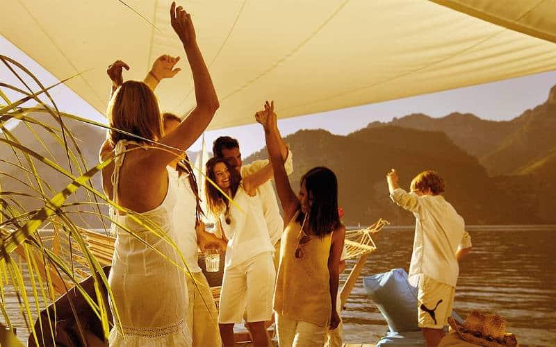 Menschen tanzen am Strand unter einem weißen Sonnensegel im Sonnenuntergang