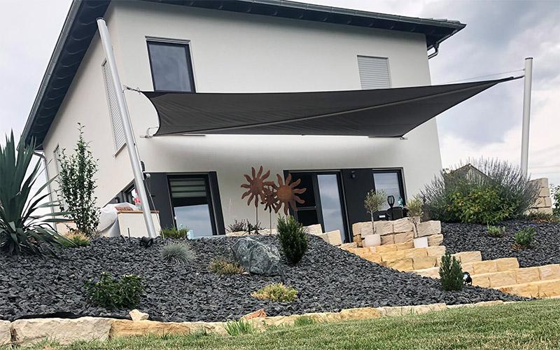 Automatisch bedienbares Sonnensegel in Schwarz an Haus und über Terrasse befestigt