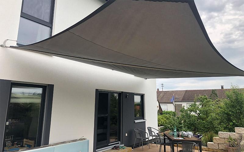 Soliday-X halbautomatisch aufrollbares Sonnensegel gespannt am Haus montiert