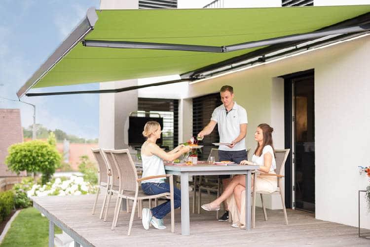 Reflexa Gelenkarmmarkise Suntigua Terrasse mit Menschen abgebildet